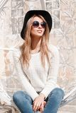 Attractive happy young hipster woman in an elegant hat in blue jeans in a knitted sweater in sunglasses posing sitting royalty free stock image