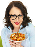 Attractive Happy Young Hispanic Woman Holding a Plate of Fusilli Tomato and Basil Pasta Royalty Free Stock Photo