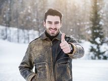 Attractive happy young man smiling, doing thumb up sign stock photography