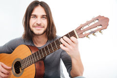 Attractive happy young man smiling and holding acoustic guitar Stock Photography