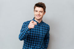 Attractive happy young man standing over grey wall and pointing. Photo of attractive happy young man standing over grey wall and pointing. Looking at camera stock photo