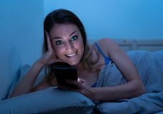Attractive happy young woman chatting on mobile phone late at nigh in bed looking cheerful and fun. Happy young beautiful girl talking and surfing on the stock photo