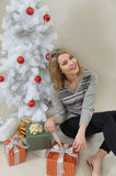 An attractive happy young woman open a gift on Christmas morning Royalty Free Stock Photos