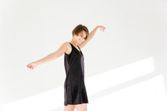 Attractive happy young woman in short black dress dancing Royalty Free Stock Photography