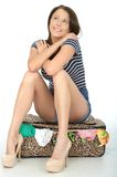 Attractive Happy Young woman Sitting on a Packed Overflowing Suitcase Royalty Free Stock Image