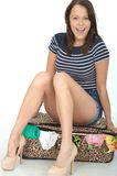 Attractive Happy Young woman Sitting on a Packed Overflowing Suitcase Stock Images