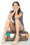 Attractive Happy Young woman Sitting on a Packed Overflowing Suitcase Stock Photo