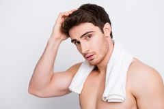 Attractive, harsh, virile, flirty, stunning, manly, confident, s. Portive macho with flawless, smooth, soft skin combing, touching his perfect hair with hand Royalty Free Stock Images