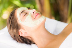 Attractive having white cream on her face at spa center Stock Photos