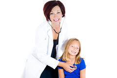 Attractive health care professional or pediatrician or nurse listening to heart and lungs exam of child with stethoscope Stock Images