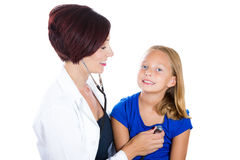 Attractive health care professional or pediatrician or nurse listening to heart and lungs exam of child with stethoscope Royalty Free Stock Images