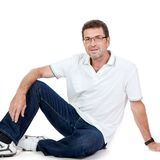 Attractive healthy adult man sitting on floor with jeans isolated Royalty Free Stock Image