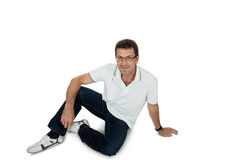 Attractive healthy adult man sitting on floor with jeans isolated Royalty Free Stock Photo