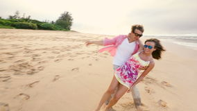 Attractive healthy couple having fun being together running on beach stock video footage