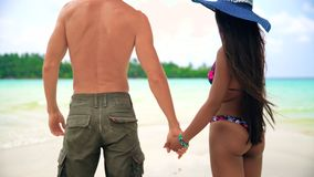 Attractive healthy couple having fun being together walking on the beach. Summer vacation, Travel and LifeStyle concept: Young Interracial couple white Caucasian stock footage