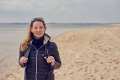 Attractive healthy woman enjoying a hike on the beach. On a cold overcast day standing smiling at the camera on the sand holding the straps of her backpack royalty free stock photo
