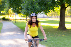 Attractive healthy woman riding a bicycle. Attractive healthy woman wearing a helmet riding a bicycle outdoors in a park approaching the camera with a smile in a royalty free stock image