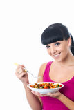 Attractive Healthy Young Woman Holding a Bowl of Fresh Colourful. Young Woman Holding or eating a fresh bowl of colourful vegetarian tomato pasta, with dark hair Stock Photography