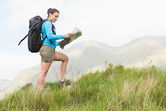 Attractive hiker with backpack walking up hill reading a map Stock Photo