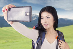 Attractive hiker taking picture with smartphone Stock Photos