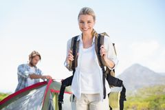 Attractive hiking blonde smiling at camera while partner pitches tent Royalty Free Stock Images
