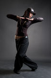 Attractive hip-hop girl dancing. Against dark background Stock Photos
