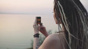 Attractive hippie woman with dreadlocks making photo on smart phone at sunset near sea