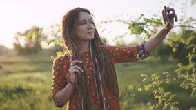 Attractive hippie woman with dreadlocks making selfie on smartphone at sunset near glade
