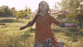 Attractive hippie woman with dreadlocks spinning and dancing slow motion 120fps. Sunset
