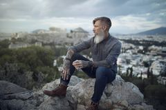 Attractive hipster with a beard is sitting on a rock high over Athens City with Acropolis view royalty free stock photo