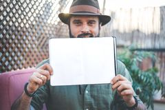 Attractive Hipster blogger holding notepad with open blank sheets on hands, while spending time on terrace of cafe.Space. For Copy paste text royalty free stock photography