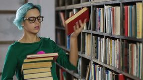 Gorgeous hipster girl in library looking for book stock footage