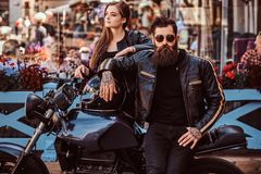 Attractive hipster couple - bearded brutal male in sunglasses dressed in a black leather jacket and his young sensual. Girl standing near, posing against Royalty Free Stock Photo