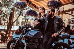 Attractive hipster couple - bearded brutal male in sunglasses dressed in a black leather jacket and his young sensual. Girl standing near, posing against Stock Image