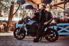 Attractive hipster couple - bearded brutal male in sunglasses dressed in a black leather jacket and his young sensual. Girl standing near, posing against Stock Photos