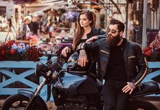 Attractive hipster couple - bearded brutal male in sunglasses dressed in a black leather jacket and his young sensual. Girl standing near, posing against Royalty Free Stock Photos