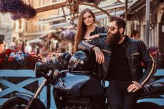 Attractive hipster couple - bearded brutal male in sunglasses dressed in a black leather jacket and his young sensual. Girl standing near, posing against Royalty Free Stock Photography