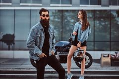 Attractive hipster couple - bearded brutal male in sunglasses dressed in a jeans jacket and his young sensual girl. Standing on steps against skyscraper Royalty Free Stock Photo