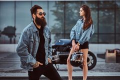 Attractive hipster couple - bearded brutal male in sunglasses dressed in a jeans jacket and his young sensual girl. Standing on steps against skyscraper Royalty Free Stock Photos
