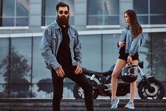 Attractive hipster couple - bearded brutal male in sunglasses dressed in a jeans jacket and his young sensual girl. Standing on steps against skyscraper Stock Photo