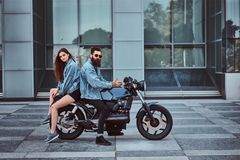 Attractive hipster couple - bearded brutal male in sunglasses and jeans jacket and his young sensual girl sitting back. To back on a retro motorcycle against a Stock Images