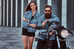 Attractive hipster couple - bearded brutal male in sunglasses and jeans jacket sitting on a retro motorcycle and his. Young sensual girl standing near, posing Stock Image