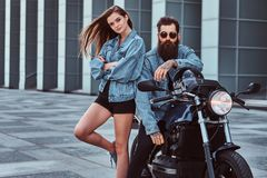 Attractive hipster couple - bearded brutal male in sunglasses and jeans jacket sitting on a retro motorcycle and his. Young sensual girl standing near, posing Royalty Free Stock Photos