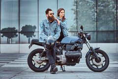 Attractive hipster couple - bearded brutal male in sunglasses and jeans jacket sitting on a retro motorcycle and his. Young sensual girl standing near, posing Stock Images
