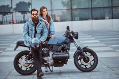Attractive hipster couple - bearded brutal male in sunglasses and jeans jacket sitting on a retro motorcycle and his. Young sensual girl standing near, posing Stock Photo