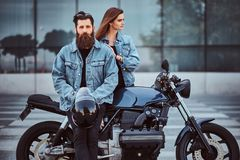 Attractive hipster couple - bearded brutal male in sunglasses and jeans jacket sitting on a retro motorcycle and his. Young sensual girl standing near, posing Royalty Free Stock Image