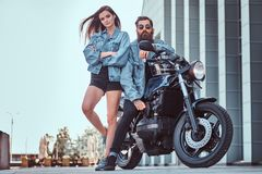 Attractive hipster couple - bearded brutal male in sunglasses and jeans jacket sitting on a retro motorcycle and his. Young sensual girl standing near, posing Royalty Free Stock Photography