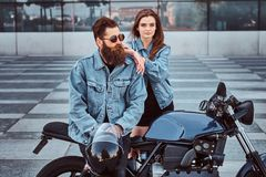 Attractive hipster couple - bearded brutal male in sunglasses and jeans jacket sitting on a retro motorcycle and his stock image