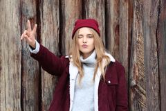 Attractive hipster girl near wooden fence stock photo