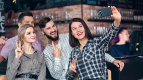 Attractive hipster girl taking selfie using smartphone surrounded by smiling friend at cozy pub. Medium shot. Group happy young people posing gesturing making stock video